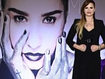 Getting a big head? Demi Lovato poses under a giant portrait of herself ahead of her Mexican concert