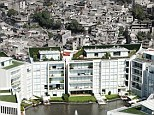 Haves and have-nots: This lavish block of apartments can be seen right next to a sea of tumbledown flats - though residents have blocked off the view
