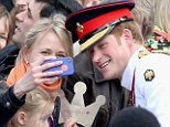 All smiles: Price Harry wins hearts and minds in Estonia, cheerfully posing for a selfie with a delighted local lady