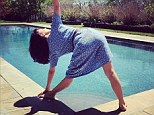 Yogi: Hilaria Baldwin strikes her daily yoga pose on Sunday in a blue floral printed dress by the pool
