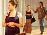 Keeping comfy! Pregnant Mila Kunis cradles her growing tum as she leaves party with fiancée Ashton Kutcher in patterned maxi skirt