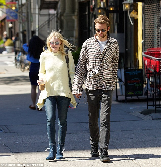Saturday stroll: Dakota - dressed in a yellow sweater, skinny blue jeans, short blue boots, and circular-framed sunglasses - sipped on an iced coffee during their walk