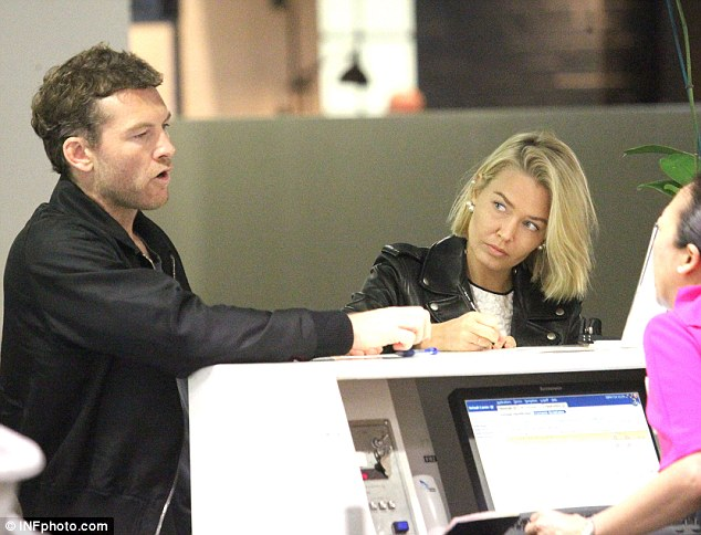 Uh-oh: A wary Bingle, 26, watches on as she continues to sign documents at the counter