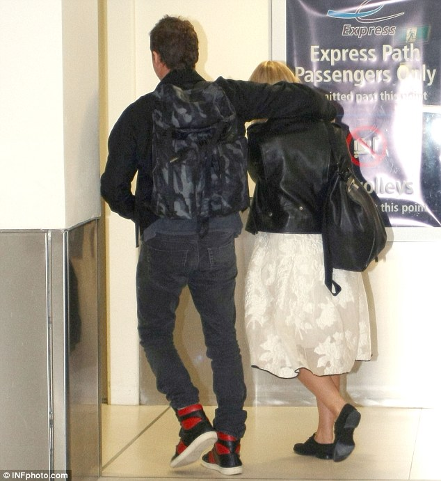 Media shy: The Australian actor protectively put his arm around his girlfriend as they headed towards their flight
