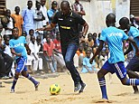 Shows his skills: Patrick Vieira enjoys a kick about with Senegalese students during a trip to Dakar