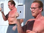 iPumped! Arnold Schwarzenegger shows off his pecs as he takes selfie on tablet during sunbathing session in Cannes
