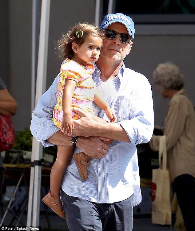 Doting dad: 59-yea-old Bruce holds on to daughter Mabel as they visit a farmers market