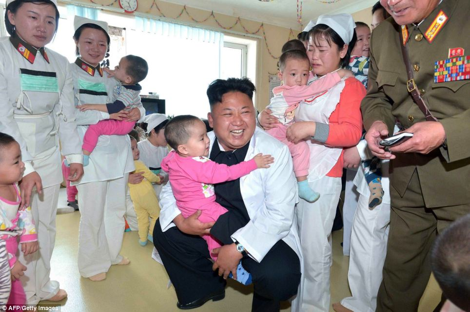 A toddler looks entertained by the visit as she clutches on to the dictator who is kitted out in a white coat, although a nurse and another little girl behind the leader look less enamored with his presence