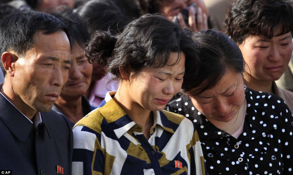 Families of victims of an accident at an apartment construction site in Pyongyang grieve during a gathering in the capital