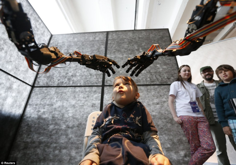 Technology amazes: A young visitor looks enchanted with the robotic arms as the child interacts with The Blind Robot from Singapore during the Robot Ball scientific exhibition which will be running in Moscow until the middle of June