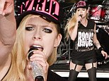 She's still the ultimate rock chick: Avril Lavigne takes to the stage in sleeveless T-shirt and suspenders