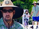 Big hat: Adam Sandler wore a wide hat on Sunday while teaching his daughter how to ride a bike in Malibu, California