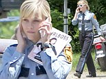 An arresting sight! Reese looks like a natural in stiff police uniform on set of new movie Don't Mess With Texas