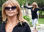 Dancing in the streets! Goldie Hawn shimmies down the street in blue leggings and a snug black sweater