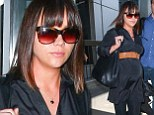 Fuelling the fire: Christina Ricci appeared to show a glimpse of a burgeoning bump as she and her husband James Heerdegen arrived at Los Angeles International Airport on Friday