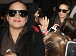 Shady lady! Demi Lovato makes cool arrival at her London hotel by wearing sunglasses despite it being dark as she is mobbed by fans
