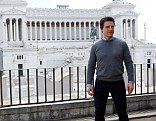 Statuesque: Tom Cruise appeared to be imitating the stone statues behind him as he posed for a photo call in Rome
