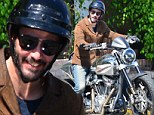 Keanu Reeves cuts an unusually cheery figure as he takes a spin on his motorbike