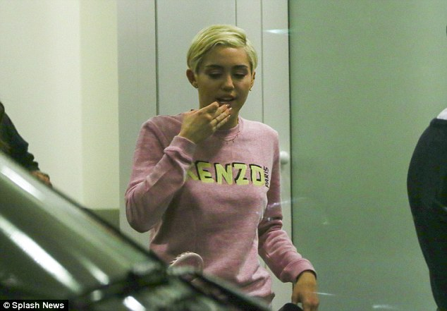 Jet set: Miley Cyrus appeared to be yawning while en route to her next stop at an airport in Cologne, Germany on Monday