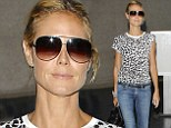 Heidi Klum shows off her slender waist and long pins in an animal print top and skinny jeans as she jets back to LA