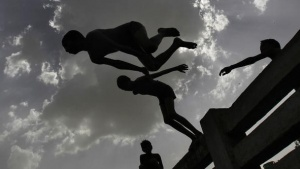 Boys jump into a canal during a hot day in New Delhi May 27, 2013. REUTERS/Anindito Mukherjee/Files