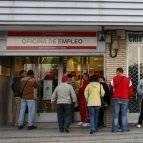 Decenas de personas hacen cola mientras esperan su turno ante una oficina del INEM.