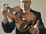 Kerry Keane, Christie's Musical Instruments specialist, poses for a photograph with the Kreutzer Stradivarius, estimated to be worth between $7.5 million and $10 million