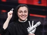 """Sister Cristina Scuccia poses with the trophy and holding the cross on the stage after winning the final of the Italian version of the TV talent show """"The Voice"""" in Milan, Italy, Thursday, June 5, 2014. With her full habit, sensible shoes and cheering nuns in her camp, Sister Cristina Scuccia made it to Thursday's finals of the Italian version of """"The Voice"""" after capturing attention, and millions of YouTube viewers, with her first-round performance in March. At left is Italian rapper Dj-AX and right Italian singer Noemi. (AP Photo/Luca Bruno)"""