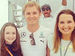 Say cheese: Lewis Hamilton (second right) photobombed Nico Rosberg's (second left) photo with two fans