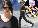 Black-clad Selena Gomez looks tough in knee-high boots and 'feels sorry for' cardboard cut out-wielding rival Miley Cyrus