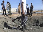 Libyan militiamen look at the site of an explosion at an army checkpoint