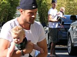 He's a handful! Josh Duhamel goes barefoot while carrying his adorable son Axl in his arms