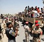 Joining the fight: Iraqi men board military trucks to join the army at the main recruiting center in Baghdad, Iraq