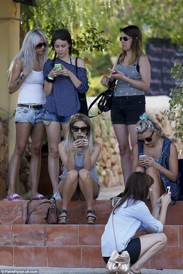 Chatty group: The ladies all seemed rather distracted by their phones as they waited on some steps