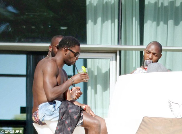 Holding court: Tinie sips a fruity looking cocktail whilke chatting with pals