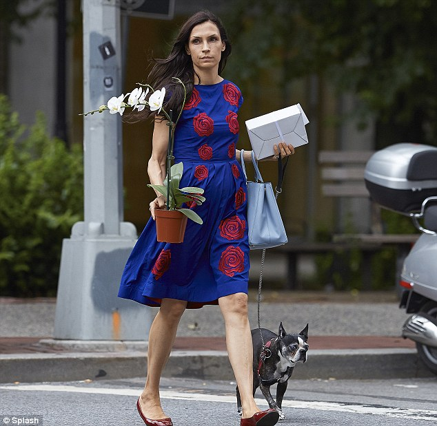 Woman on the go! The former fashion model juggled holding her pup, a pot-plant, handbag and a package.