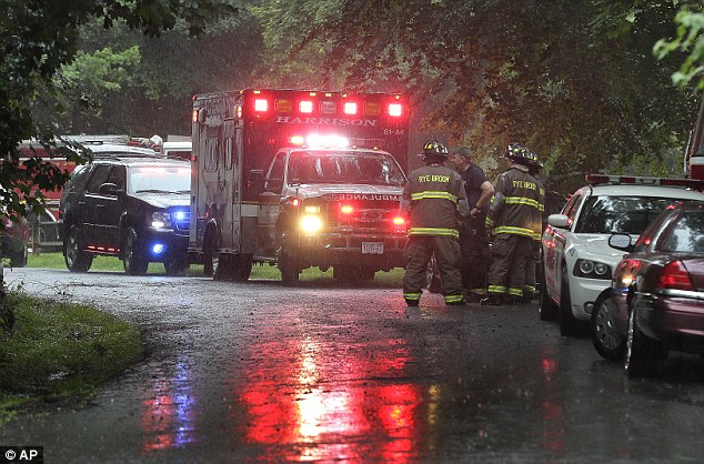 Emergency vehicles and personnel stand near a command post set up for a small plane that crashed on a road just west of Westchester County Airport today