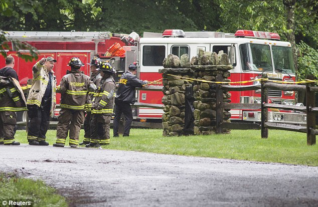 Police and firefighters stand near the site of a small plane crash in the town of Harrison, Westchester County, New York, today
