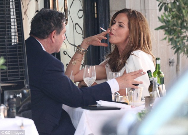 Chilling out: Both stars also enjoyed a relaxing puff on a cigarette as they sat at the table