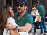 Gerard Butler gives mystery brunette into a tight hug and kisses her on the cheek as the pair make their way into his New York hotel