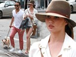 Chrissy Teigen shows off her long legs in tiny denim shorts as she and John Legend enjoy a stroll with their pet pooch