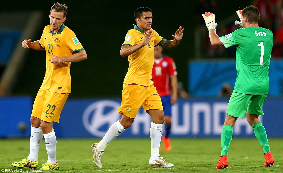 Cahill celebrates with teammates after scoring a goal for Australia towards the end of the first half