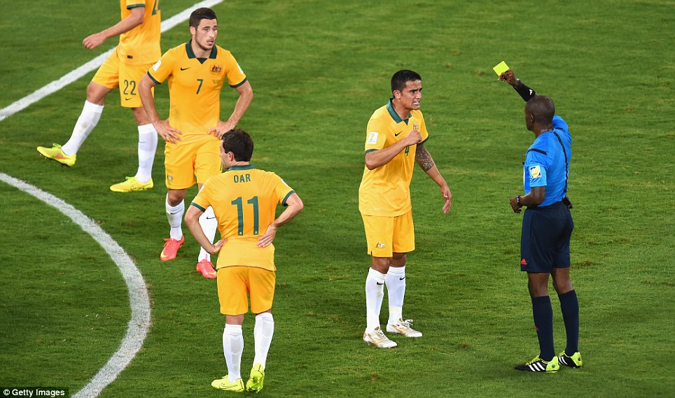 Referee Noumandiez Doue shows Cahill a yellow card