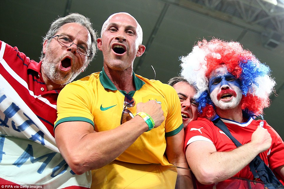 An Australian fan in green and gold cheers on his team among a sea of Chile fans before the game kicked off