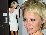 Famous assets: Pamela Anderson bore her ample cleavage in a plunging white knit top with a matching pencil skirt on Friday evening