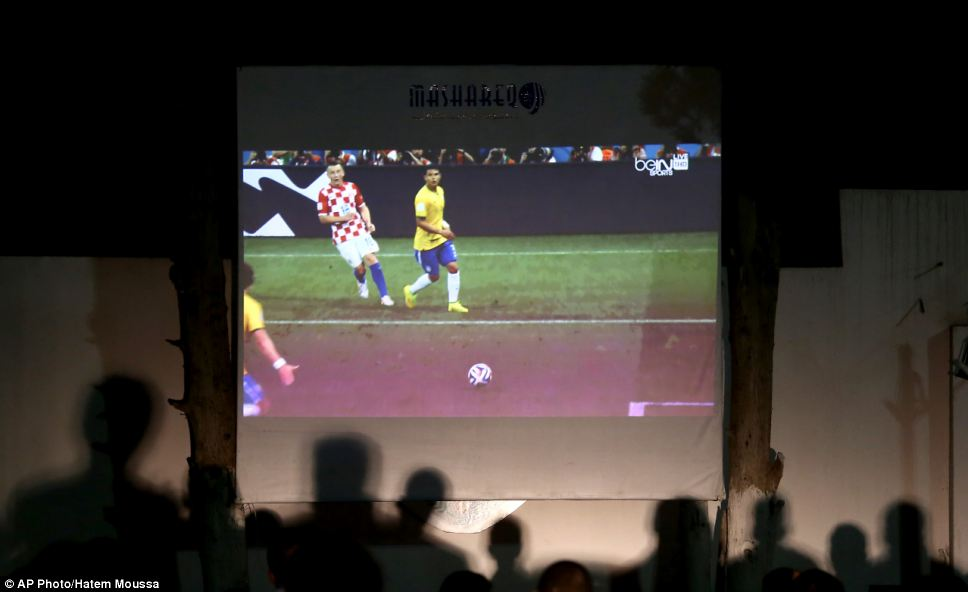 Palestinians watch the opening match of the World Cup 2014 on a huge screen in Gaza sports club in Gaza City