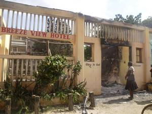A woman observes the remains of the Breeze View Hotel, where residents watching World Cup soccer tournament, were attacked and killed by militants, in the town of Mpeketoni, about 100 kilometers (60 miles) from the Somali border on the coast of Kenya