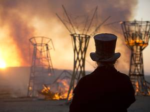 A man looks at a wooden sculpture that was set on fire during Israel's first Midburn Festival, modeled after the popular Burning Man Festival held annually in Nevada's Black Rock Desert, near the Israeli kibbutz of Sde Boker
