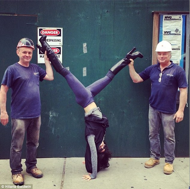 Helping hand: Two construction workers aided the yogini in an acrobatic posture in New York on Thursday