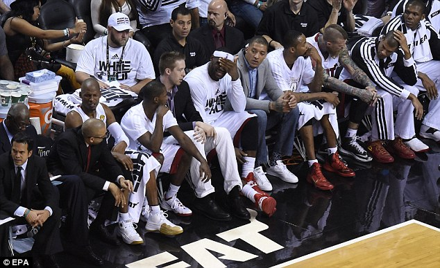 Can't bear to watch: LeBron James covers his face as the Heat bench their side go down to the Spurs
